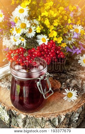 The juice from the berries of viburnum in glass containers on a napkin next to a bouquet of wild flowers on a wooden stand. Rustic. The vertical frame.