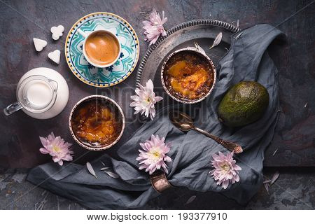 Creme brulee , cup of coffee , milk , avocado and flowers on the stone background top view