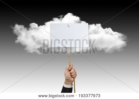 A businessman's hand holds a rope attached to a cloud on which there is a sign on a degraded ground