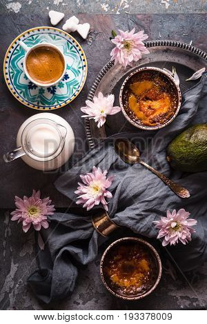 Creme brulee , cup of coffee , milk , avocado and flowers on the stone background top view vertical