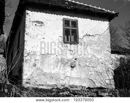 Abandoned house in Serbia. Old Serbian abandoned mountain village house. Black and white. With film grain.