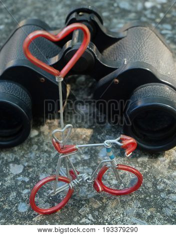 Classic Metallic Black Binoculars or Field Glasses and Bicycle Figure with Red Heart Romantic Concept for Find A Love From Far Away.