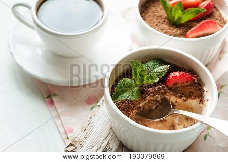 Tiramisu with strawberry and mint in the ramekins on the white table horizontal
