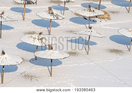 Winter on the beach. Frozen beach. Snow on the sand and parasol. Sunshades covered by snow and ice. Novi Sad, Serbia.