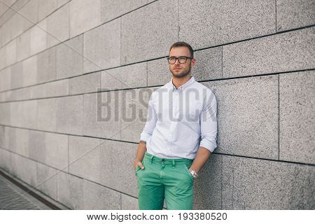 Cheerful young handsome man in sunglasses keeping hands in pockets and looking away with smile while standing against grey background. Stylish concentrated man.