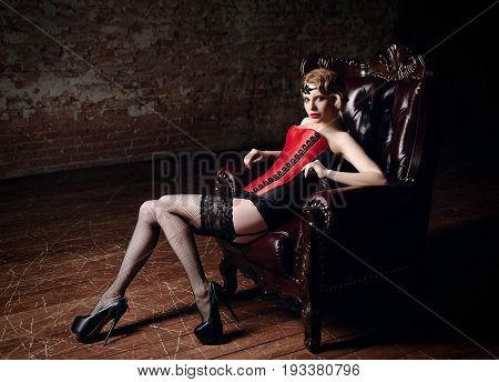 Sexy beautiful young girl dressed in a corset stockings and panties sitting in chair. Retro (vintage) style