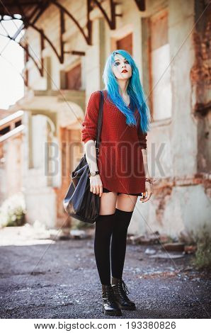 Portrait of attractive blue-haired grunge (rock) girl among the industrial ruins. Full length