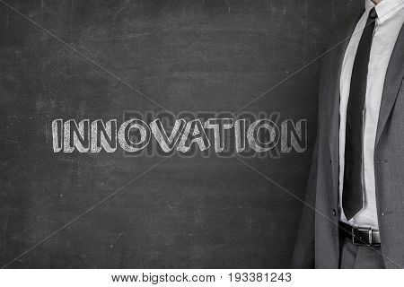 Midsection of businessman standing by innovation text on blackboard