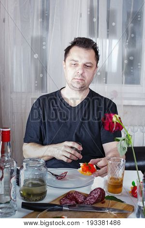 Drunk Unshaven Sad Man Sits At A Table With Drinks And Snacks, Holding A Glass And A Sandwich With C