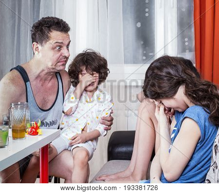 Drunk inadequate father angrily looking at their children.