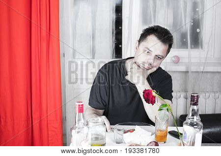 Drunk sad  not shaven man propped his head thoughtfully looking at the table with drinks and snacks.