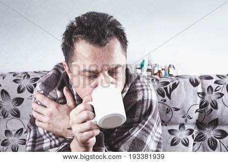 Fifty Unshaven Sick Man Drinks From A Mug. Behind Are Drugs.