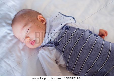 Cute little Asian 5 months old baby boy child in long dungarees and white t-shirt costume wearing bib sleeping mouth open on white sheet on bed in bedroom at home