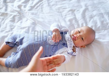 Cute smiling little Asian 6 months old baby boy child lying in long dungarees holding mothers hand on bed in bedroom at home with copy space. Family and love concept. Selective focus