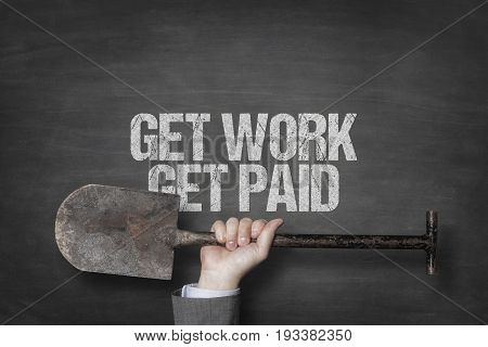 Cropped hand of businessman holding shovel under text on blackboard