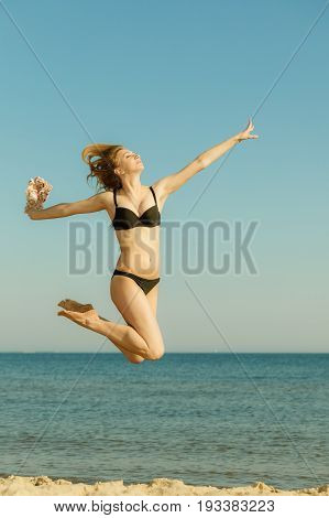 Summertime fun conept. Woman wearing bikini playing and jumping near sea enjoying summer vacations.