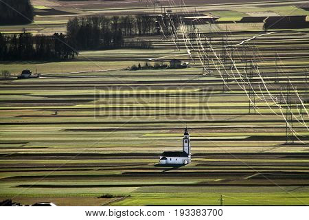 The church of Saint Ursula among green fields and power lines Slovenia.