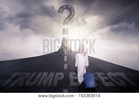 Rear of Arab male carrying a briefcase and luggage while walking on the highway with a question mark and text of Trump Effect on the asphalt