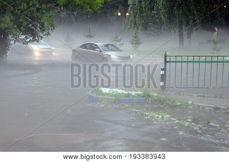 KOROLEV, MOSCOW REGION, RUSSIA - JUNE 30, 2017: Cars drive down the flooded street after a hailstorm