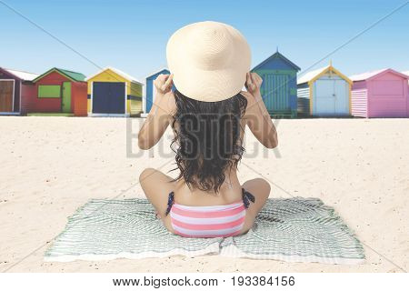 Summer Concept. Back view of young woman with long hair sitting on the beach while wearing swimsuit and straw hat. Shot with beach huts background