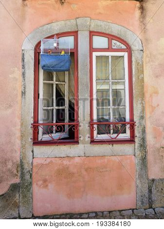 Old plastered facade of house with open window and cage with canary bird inside romantic old Alfama. Lisbon Portugal