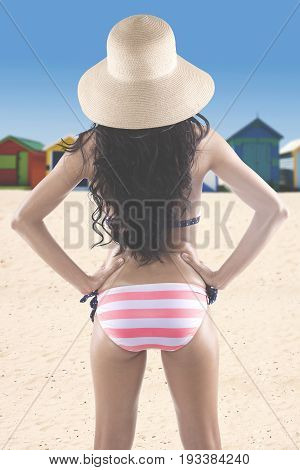 Summer Concept. Backside of a young woman with long hair standing on the beach while wearing a striped bikini and straw hat with beach huts background