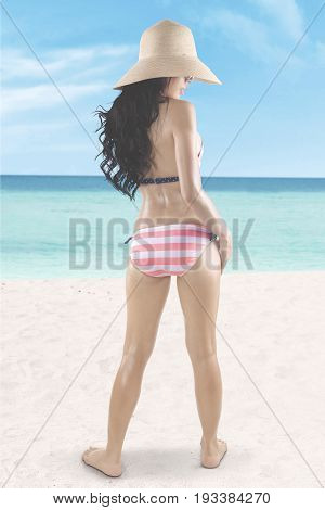 Summer Concept. Backside of a young woman with long hair and beautiful body standing and posing on the beach while wearing a striped swimsuit and straw hat