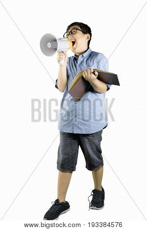 Full length of boy student speaking on megaphone while holding a book isolated on white background