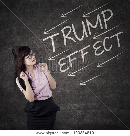 Image of frightened businesswoman with word of Trump Effect and arrows on the blackboard