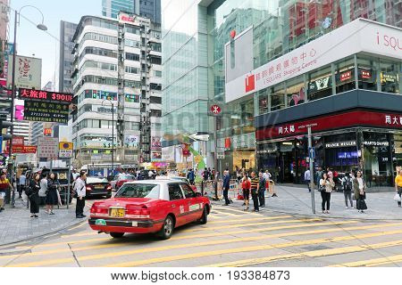 HONG KONG CHINA - APRIL 27; Busy street in Hong Kong with traffic and many pedestrians crossing the road in Hong Kong China - April 27 2017: Traditional red taxi and other cars on one of busy city junctions.
