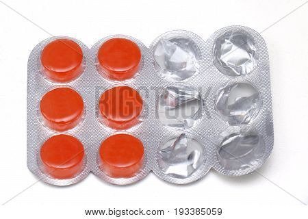 Orange flavour sore throat lozenges in silver packaging