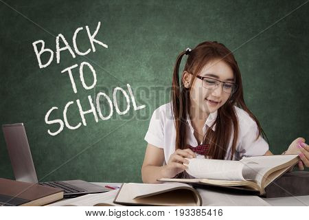 Concept of Back to School. Portrait of a clever female high school student reading literature on the table with a text Back to School on the blackboard
