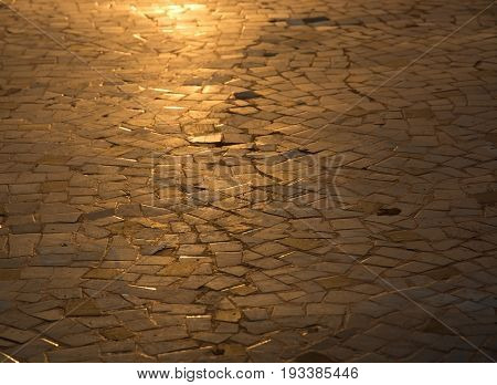 Golden sunlit mosaic or cobblestones background with partial focus and blur.