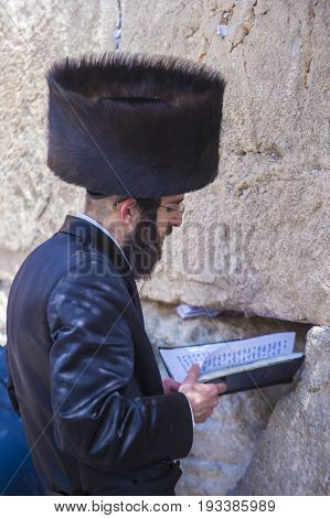 JERUSALEM - APRIL 13 : Orthodox jewish man prays in The western wall during Passover on April 13 2017 The Western wall is important Jewish religious site located in the Old City of Jerusalem