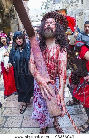 JERUSALEM - APRIL 14 : Christian pilgrims re-enact the crucifixtion of Jesus along the Via Dolorosa in Jerusalem during Good friday on April 14 2017