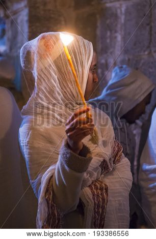 JERUSALEM - APRIL 15 : Ethiopian Orthodox pilgrim participates in the Holy fire ceremony at the Ethiopian section of the Holy Sepulcher in Jerusalm Israel on April 15 2017