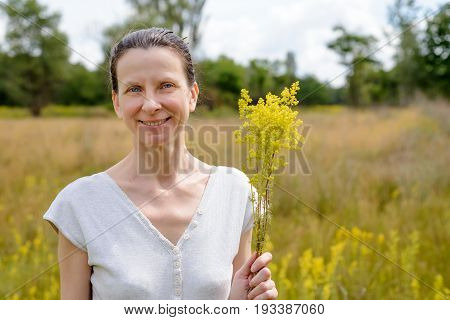 Woman Standing In A Field Of Galium Verum