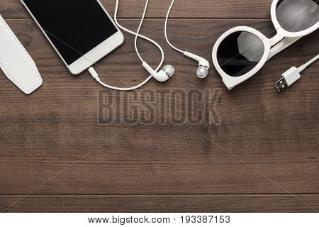studio shot of white accessories: sunglasses smart phone and earbuds. white accessories on brown table. top view of white accessories. photo of white accessories on wooden background with copy space
