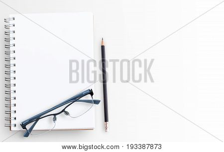 Blank paper notebook and glasses on white table background. Top view with copy space (selective focus). Office desk table concept..Office supplies and gadgets on desk table.Flat lay photo.