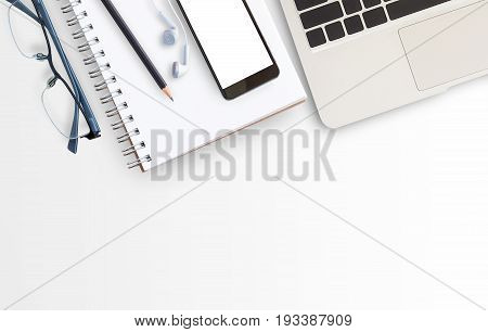 Blank paper notebook laptop computerglasses and smart phone on white table background. Top view with copy space (selective focus). Office desk table concept.Office supplies and gadgets on desk table.Flat lay photo.
