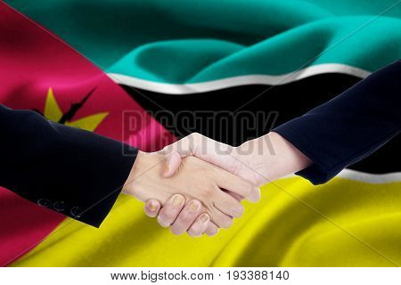 Picture of two businesspeople hands in a formal suit closing a meeting and shaking hands with Mozambique flag background
