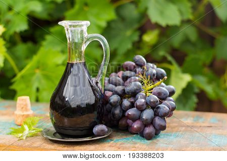Black Old Balsamic Vinegar In A Glass Jug With Fresh Red Grapes On Green Vineyard Background