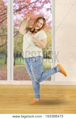 Portrait of overweight blonde woman reading a sms message with happy expression shot at home with autumn background on the window