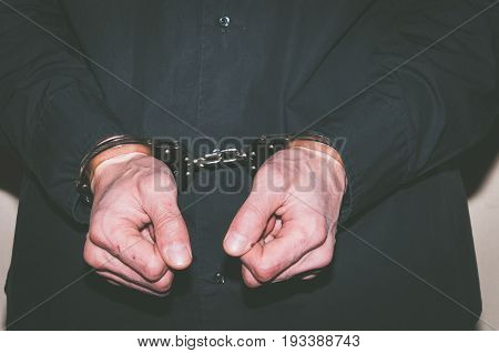 Hands with handcuffs. Hands of criminal man in black shirt. Arrested criminal man.