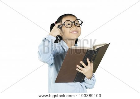 Little student wearing glasses thinking an idea while holding a textbook isolated on white background