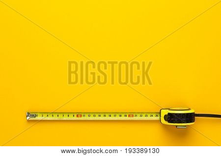 tape measure on the yellow background. tape measure with copy space. top view of tape measure. pulled out yellow tape mesure