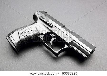 Metal black handgun on a black background