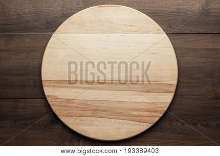 top view of wooden round board for pizza. wooden round board for pizza on brown table. round board for pizza on the wooden background. wooden round board for pizza with copy space