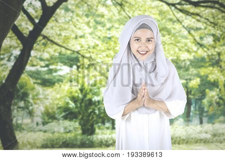 Pretty Muslim woman smiling at the camera with welcoming gestures while standing in the park