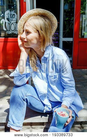 Beautiful Blonde Hair Girl In Jeans Wear With Straw Hat And Cup Of Cappuccino